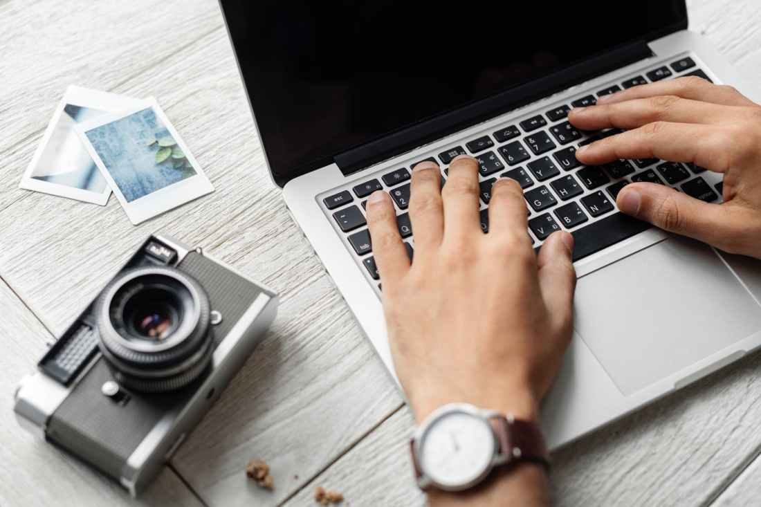 person using macbook pro beside grey camera on table